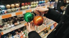 选择圣诞树的一个女孩的手多彩多姿的球在市场上 妇女是bying五颜六色 股票录像