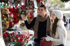 选择圣诞节纪念品的愉快的夫妇 免版税库存照片