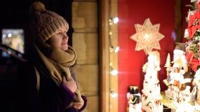选择圣诞节装饰的女孩在商店在冬日 免版税库存照片
