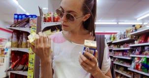 选择在两个箱子之间的年轻女人在商店 影视素材