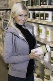 选择在五金店的产品之间的妇女 免版税库存图片