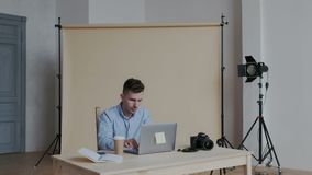 选择在他的膝上型计算机的男性自由职业者的图表设计师照片在当代内部 他修饰的图象,微笑 股票视频