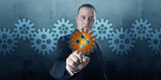 选择在传动机构的企业家一个嵌齿轮 库存照片