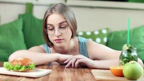 选择在健康新鲜的产品和有害的便当之间的生气年轻美女 影视素材