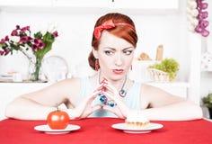 选择在健康食物和蛋糕之间的妇女 库存图片