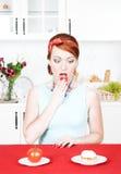选择在健康食物和蛋糕之间的妇女 免版税图库摄影