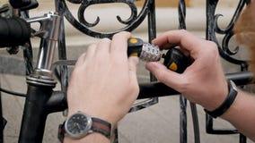 选择在号码锁的人特写镜头照片代码巩固他的在街道上的自行车 库存图片