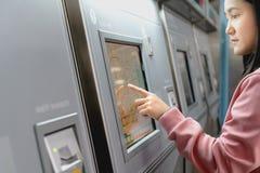 选择在地铁票机器的妇女目的地 运输概念 免版税库存照片