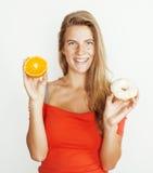 选择在多福饼和橙色果子之间的年轻白肤金发的妇女隔绝在白色背景,生活方式人概念 免版税库存照片