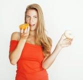 选择在多福饼和橙色果子之间的年轻白肤金发的妇女隔绝在白色背景,生活方式人概念 免版税图库摄影