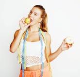 选择在多福饼和苹果果子之间的年轻白肤金发的妇女隔绝在白色背景,生活方式人概念 库存照片