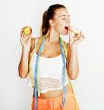 选择在多福饼和苹果果子之间的年轻白肤金发的妇女隔绝在白色背景,生活方式人概念 库存图片