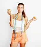 选择在多福饼和苹果果子之间的年轻白肤金发的妇女隔绝在白色背景,生活方式人概念 免版税库存图片
