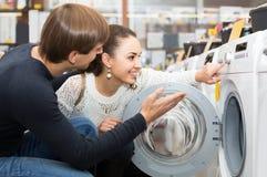 选择在大型超级市场和微笑的夫妇洗衣机 库存照片