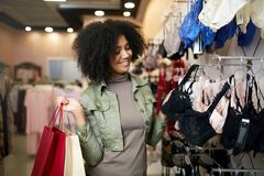 选择在女用贴身内衣裤商店精品店的年轻人微笑的可爱的非裔美国人的妇女正确的胸罩大小 黑混合的族种 免版税库存照片