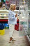 选择在开放冰箱的妇女产品有牛奶店的 库存图片