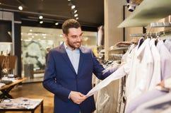 选择在服装店的愉快的年轻人衣裳 免版税图库摄影