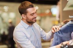 选择在服装店的愉快的年轻人衣裳 免版税库存图片