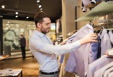 选择在服装店的愉快的年轻人衣裳 库存照片