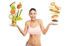 选择在沙拉和快餐之间的美丽的妇女 免版税库存图片