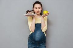 选择在甜蛋糕和苹果之间的怀孕的夫人 库存照片