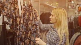 选择在百货商店的女孩的特写镜头一件礼服 库存照片