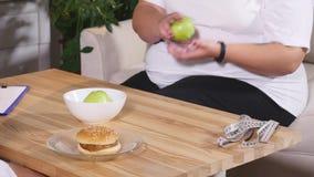 选择在苹果和汉堡之间的肥胖妇女 饮食和健康 股票录像