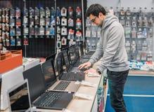 选择在计算机商店的现代男性顾客膝上型计算机 免版税库存照片