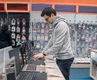 选择在计算机商店的现代男性顾客膝上型计算机 库存图片