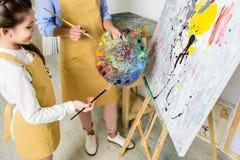 选择在调色板的老师和学生的播种的图象油漆在车间  图库摄影