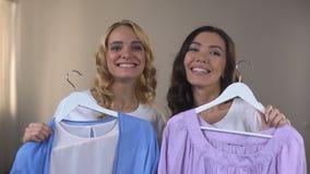选择在购物的女人,适合的室,成套装备的两个微笑的女性朋友衣裳 影视素材