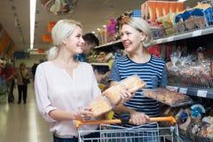 选择在超级市场的面包店部分的成熟妇女酥皮点心 库存照片