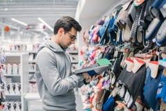 选择在超级市场购物中心的顾客人家庭拖鞋 免版税库存照片