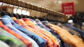 选择在销售机架的顾客五颜六色的精神衬衣 寻找男朋友的少妇礼物在衣物商店 4K 影视素材