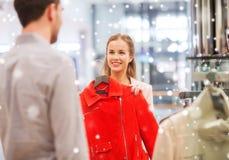 选择在购物中心的愉快的年轻夫妇衣裳 免版税库存照片