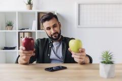 选择在绿色和红色苹果之间的有胡子的商人,当坐在办公室桌上时 免版税图库摄影