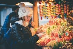 选择在C的愉快的美丽的妇女传统假日糖果 免版税库存照片