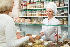 选择坚果的卖主和顾客画象  免版税库存图片