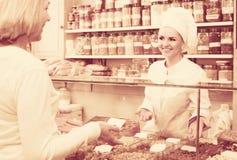 选择坚果的卖主和顾客画象  库存照片