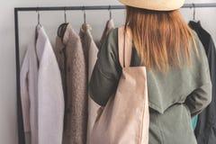 选择外套的妇女在商店 免版税库存图片