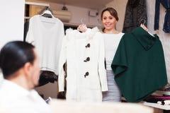 选择外套的普通的夫妇在商店 免版税库存图片