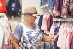 选择婴孩的年长妇女在商店穿衣 免版税库存图片