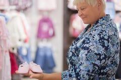选择婴孩的年长妇女祖母在商店穿衣 免版税库存照片