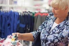 选择婴孩的年长妇女祖母在商店穿衣 库存照片
