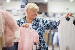 选择婴孩的年长妇女祖母在商店穿衣 图库摄影