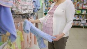 选择婴孩紧身衣裤的孕妇在服装店 股票录像