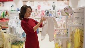 选择婴孩衣裳或儿童` s穿戴的妇女在商店 股票录像