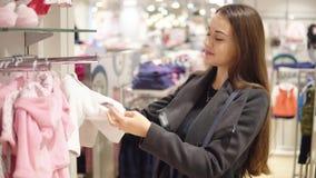 选择婴孩衣裳的顾客妇女在商店 影视素材