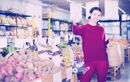 选择季节性菜的年轻深色的妇女在农厂商店 免版税库存照片