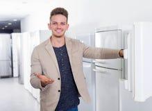 选择家用冰箱的愉快的年轻人 库存图片